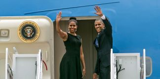 Michelle and Barack Obama waving from airplane door (© AP Images)