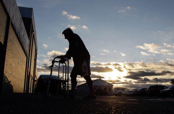 Hombre con caminador se dirige hacia un edificio en la oscuridad (© AP Images)
