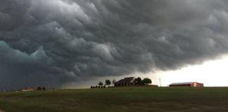 Nuvens de tempestade pairam sobre uma casa rural em uma paisagem plana (© AP Images)