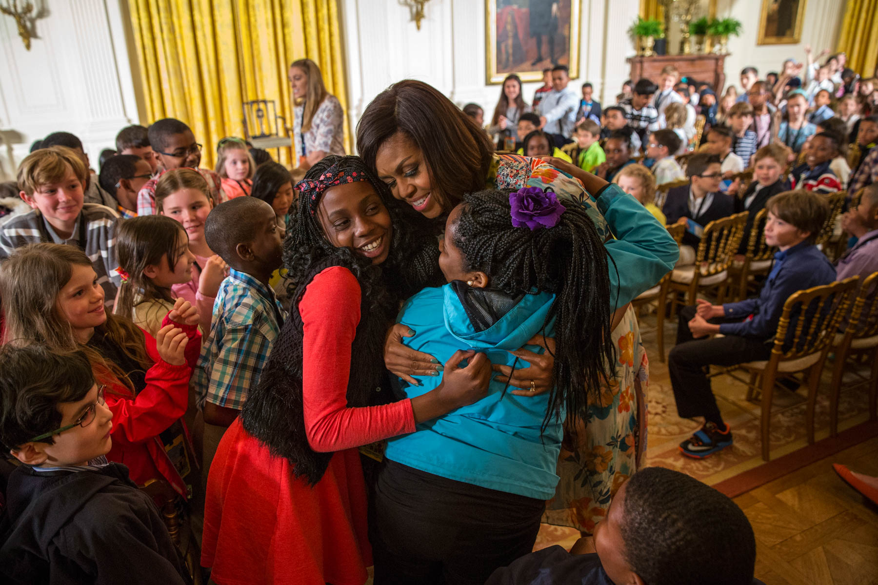 Michelle Obama hugging young girls in room full of children (© AP Images)