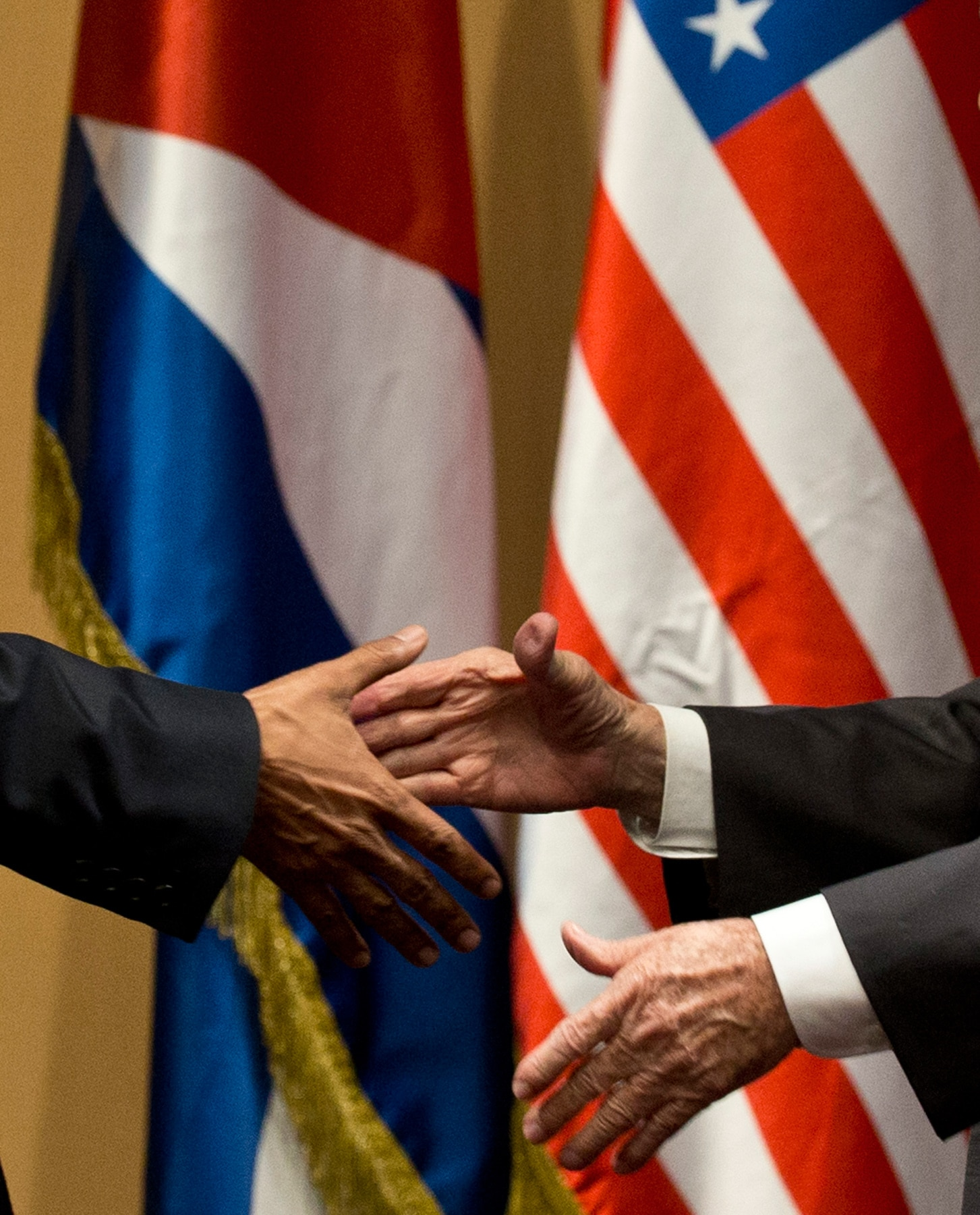 Hands reaching out to shake, with Cuban and U.S. flags in background (© AP Images)