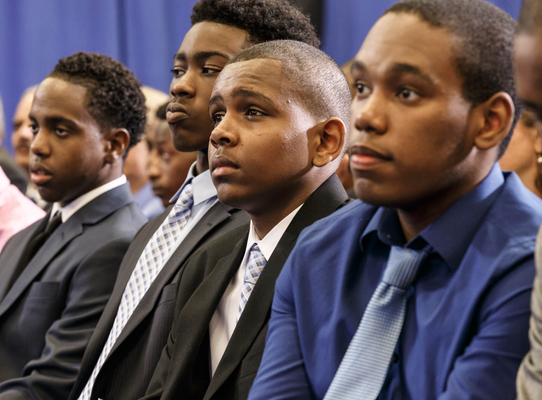 Group of young black men in audience wearing suits (© AP Images)