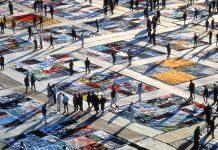 People walking around large artworks lying on ground (© AP Images)