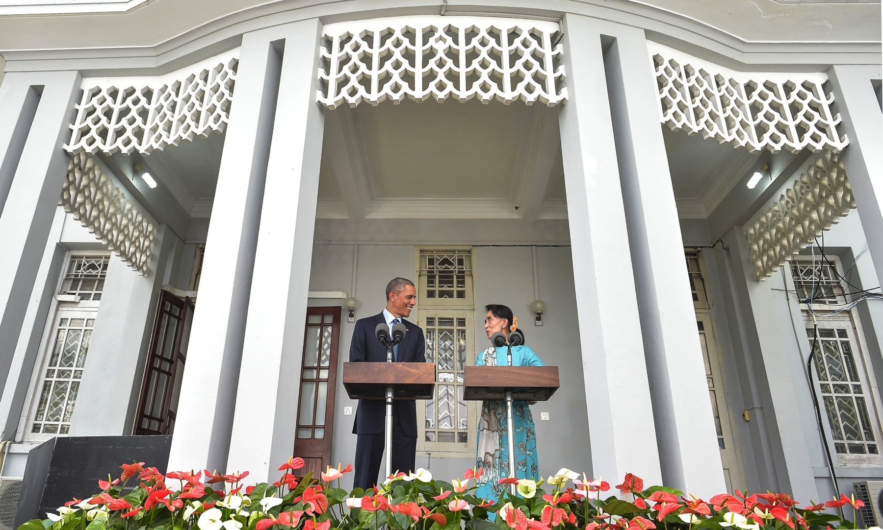 President Obama and Aung San Suu Kyi at podiums on porch of building with white columns (© Getty Images/Mandel Ngan)