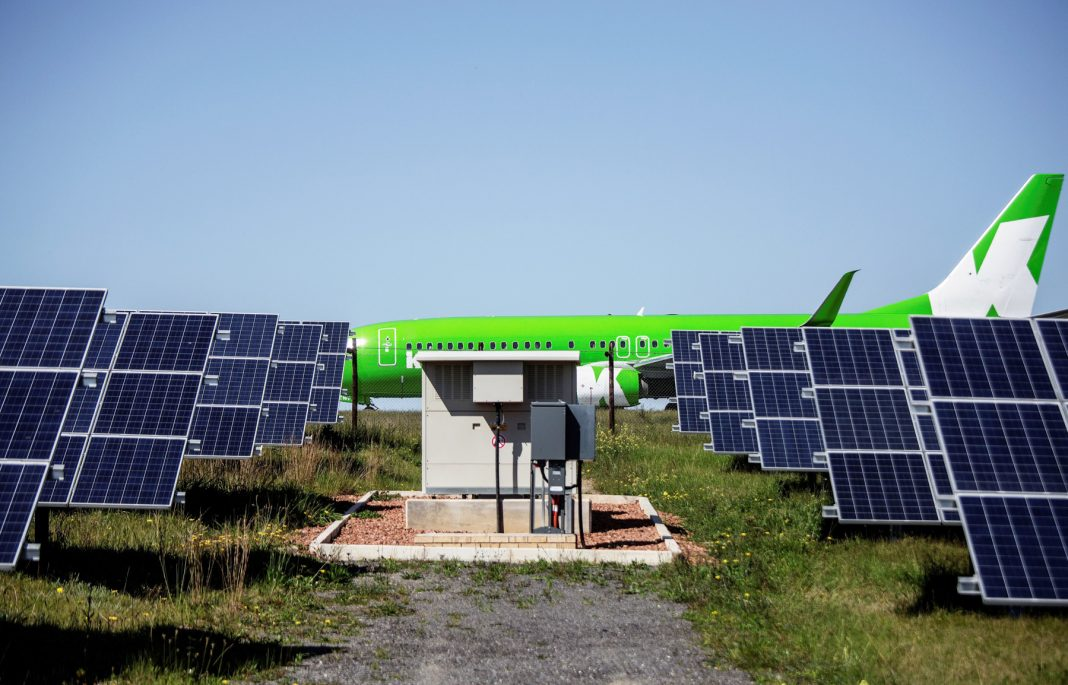 A passenger jet with solar panels in foreground (Getty Images)