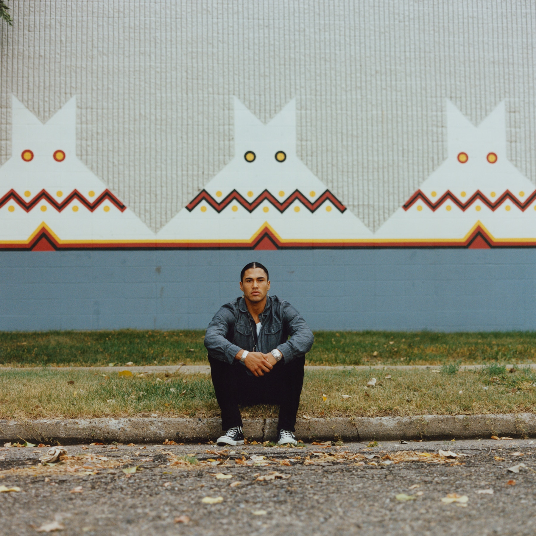 Man sitting on a curb in front of a mural of Native American art (© Carlotta Cardana/The Red Road Project)