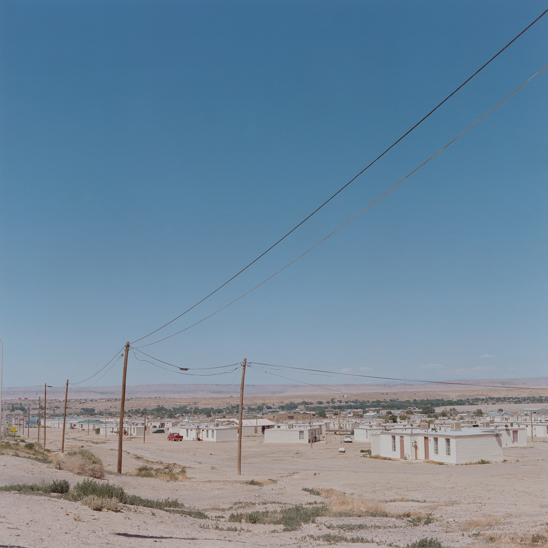 Short white buildings and utility poles and electrical wires in the desert (© Carlotta Cardana/The Red Road Project)