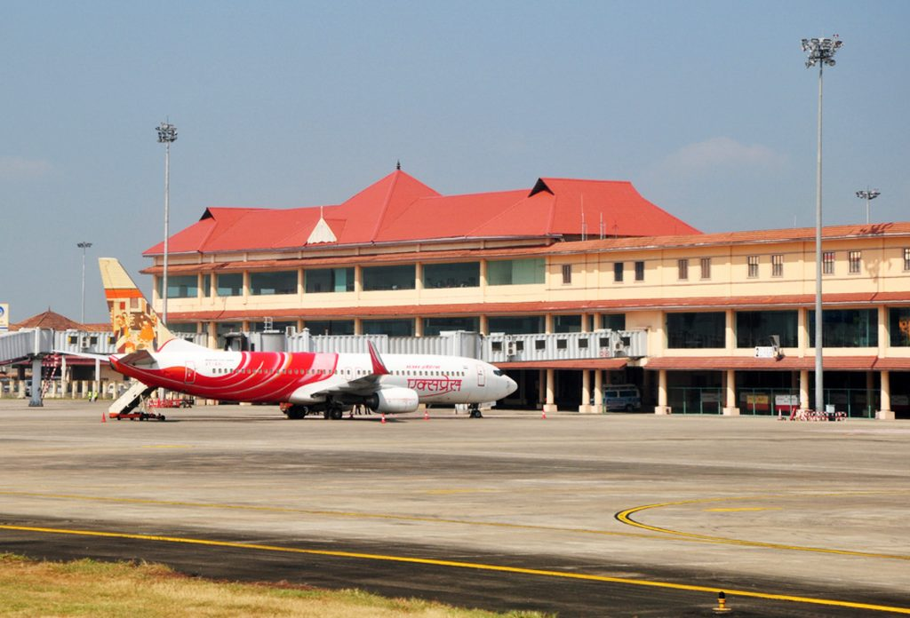 View of Cochin International Airport with plane on tarmac in front of building (Shutterstock)