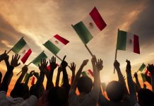 Crowd of people waving arms and Mexican flags (Shutterstock)