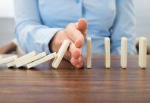Tangan menghentikan domino agar tidak roboh (Shutterstock)