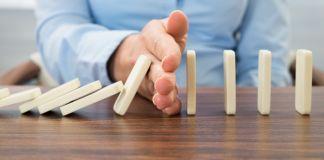 Mão impede dominós de cair (Shutterstock)