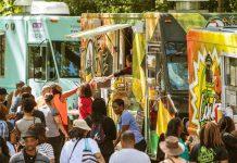 Crowd of people gathering around food trucks on the street (Shutterstock)