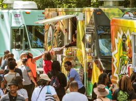 Crowd of people gathering around food trucks on the street (Shutterstock)