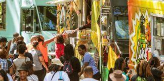 Multidão de pessoas reunidas em torno de food trucks na rua (Shutterstock)