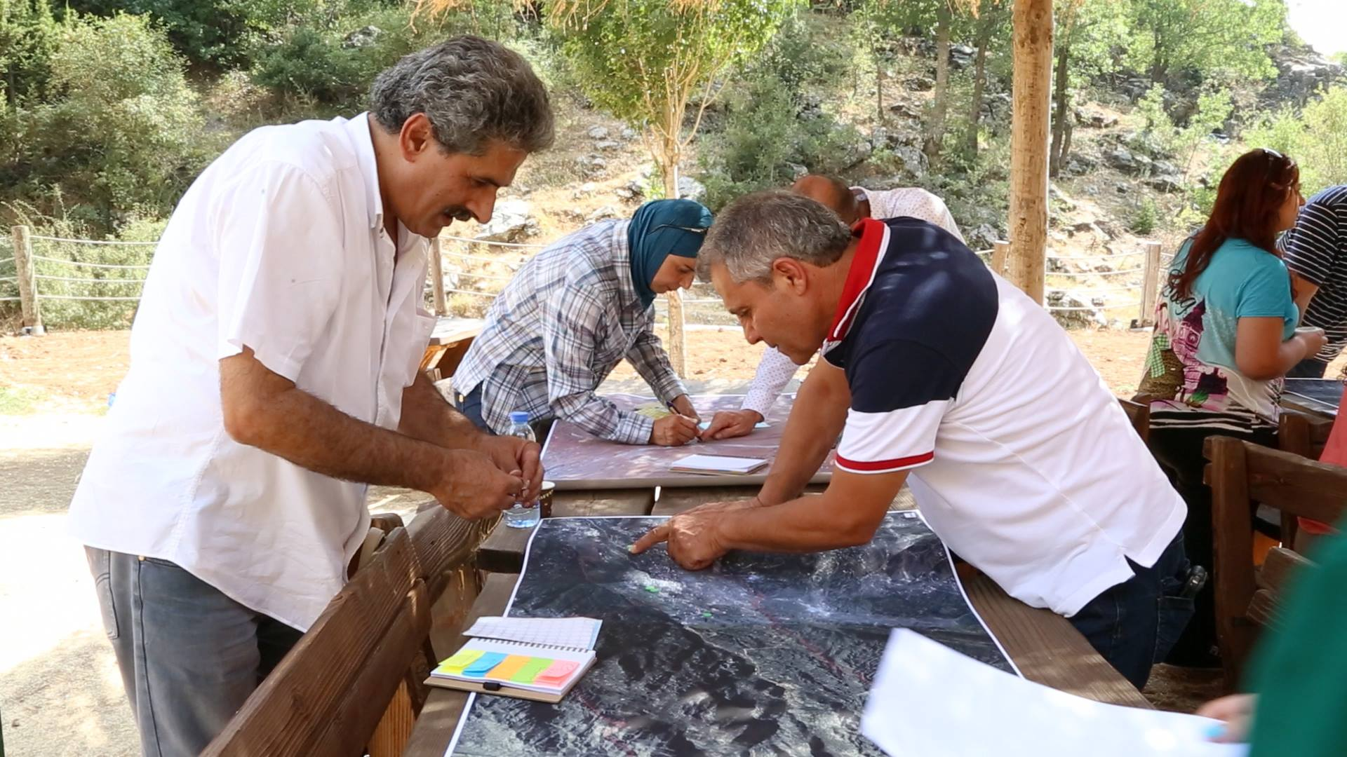 Group of people studying maps on open-air tables (Courtesy of the Lebanon Reforestation Initiative)