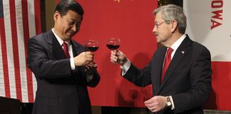 Xi Jinping and Terry Branstad raising wine glasses for toast (© AP Images)