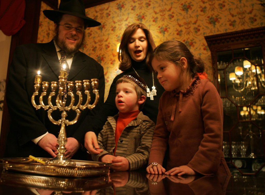 Four people celebrating Hanukkah (© AP Images)