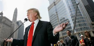Donald Trump habla ante un micrófono fuera de un edificio (© AP Images)