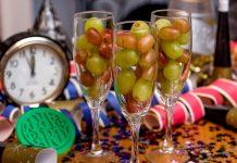 Trois flûtes à champagne remplies de grains de raisin avec un réveil à minuit moins cinq en arrière-plan (© AP Images)