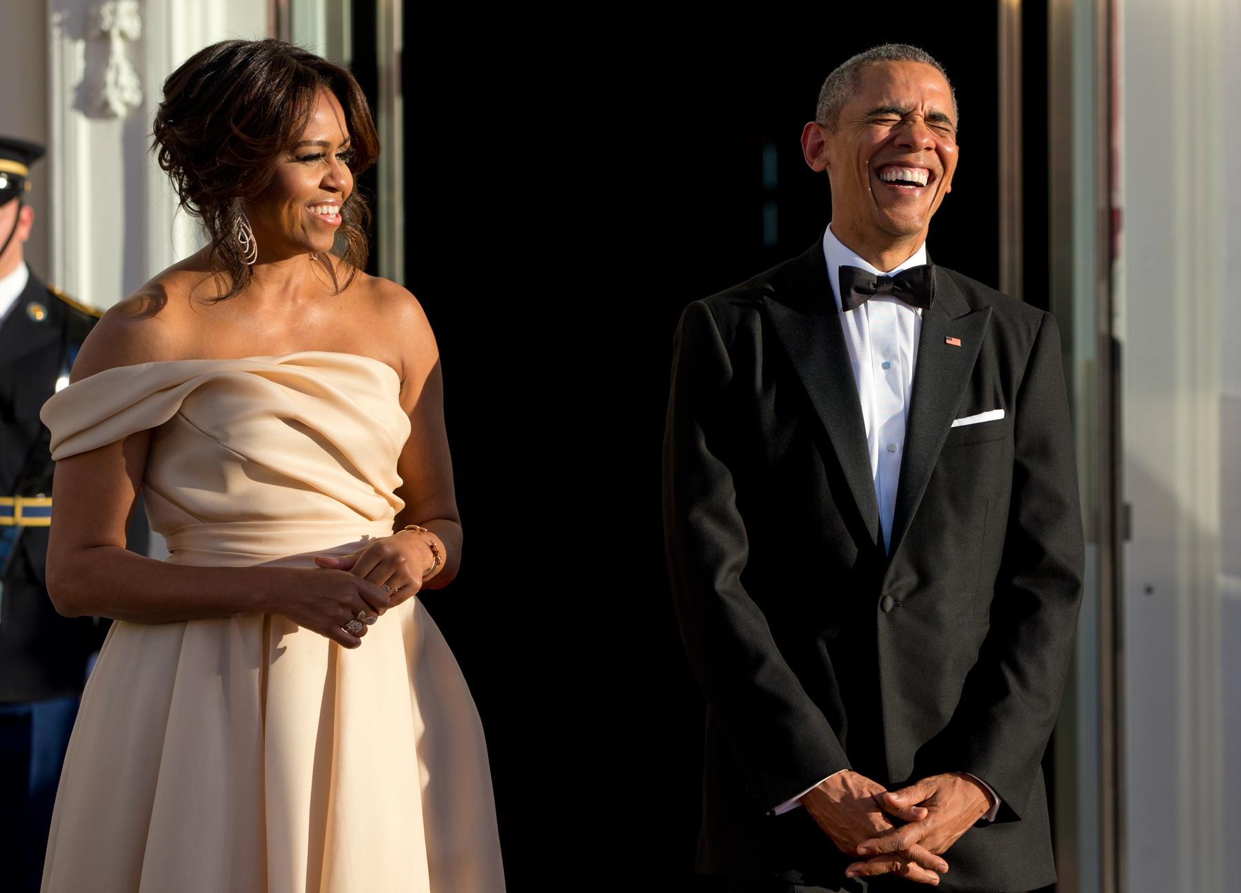Barack Obama riéndose con Michelle Obama (© AP Images)
