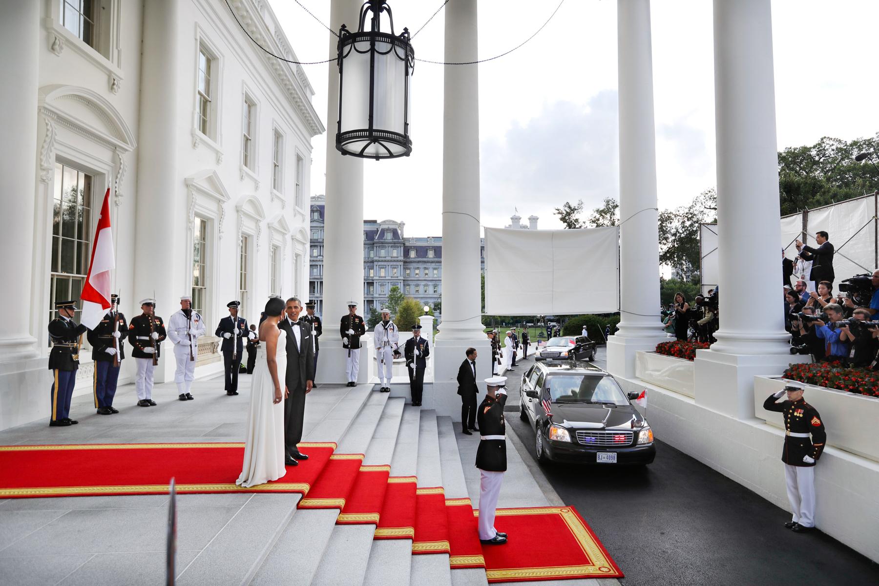 El presidente Obama y Michelle Obama, parados en la alfombra roja frente a la escalinata de entrada de la Casa Blanca, a la llegada de un auto (© AP Images)