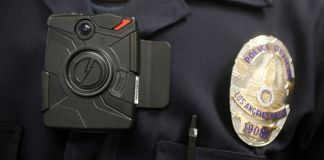 Police officer wearing body camera (© AP Images)