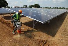Trabalhador com capacete de proteção trabalha próximo de painéis solares (© AP Images)