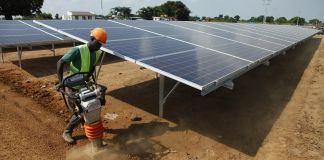 Worker in hard hat operating power tamper next to solar panel array (© AP Images)