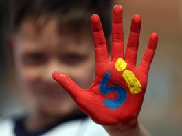 Boy with painted hand (© AP Images)