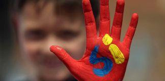 """يد صبي مصبوغة باللون الأحمر وعليها كلمة """"نعم"""" مكتوبة بالإسبانية (© AP Images)"""