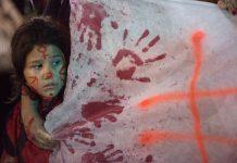 Une fillette avec des symboles peints sur le visage, à côté d'une banderole (© AP Images)