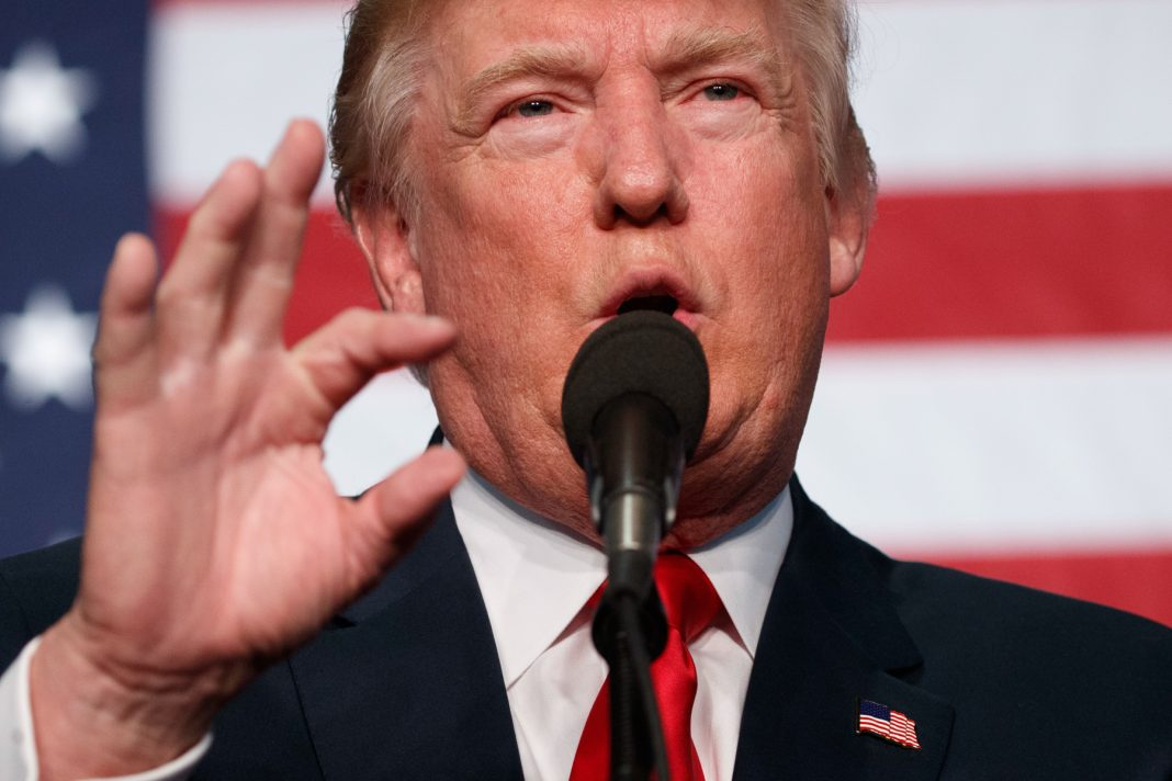 Donald Trump speaking into microphone (© AP Images)