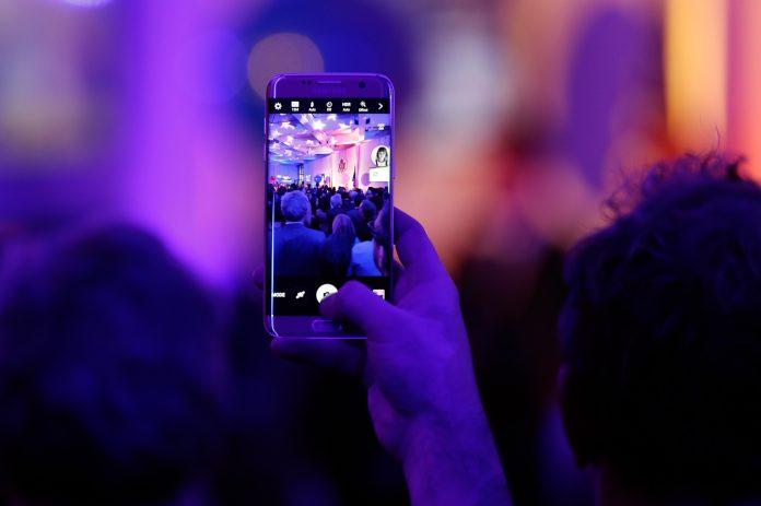 Hand holding cellphone aloft