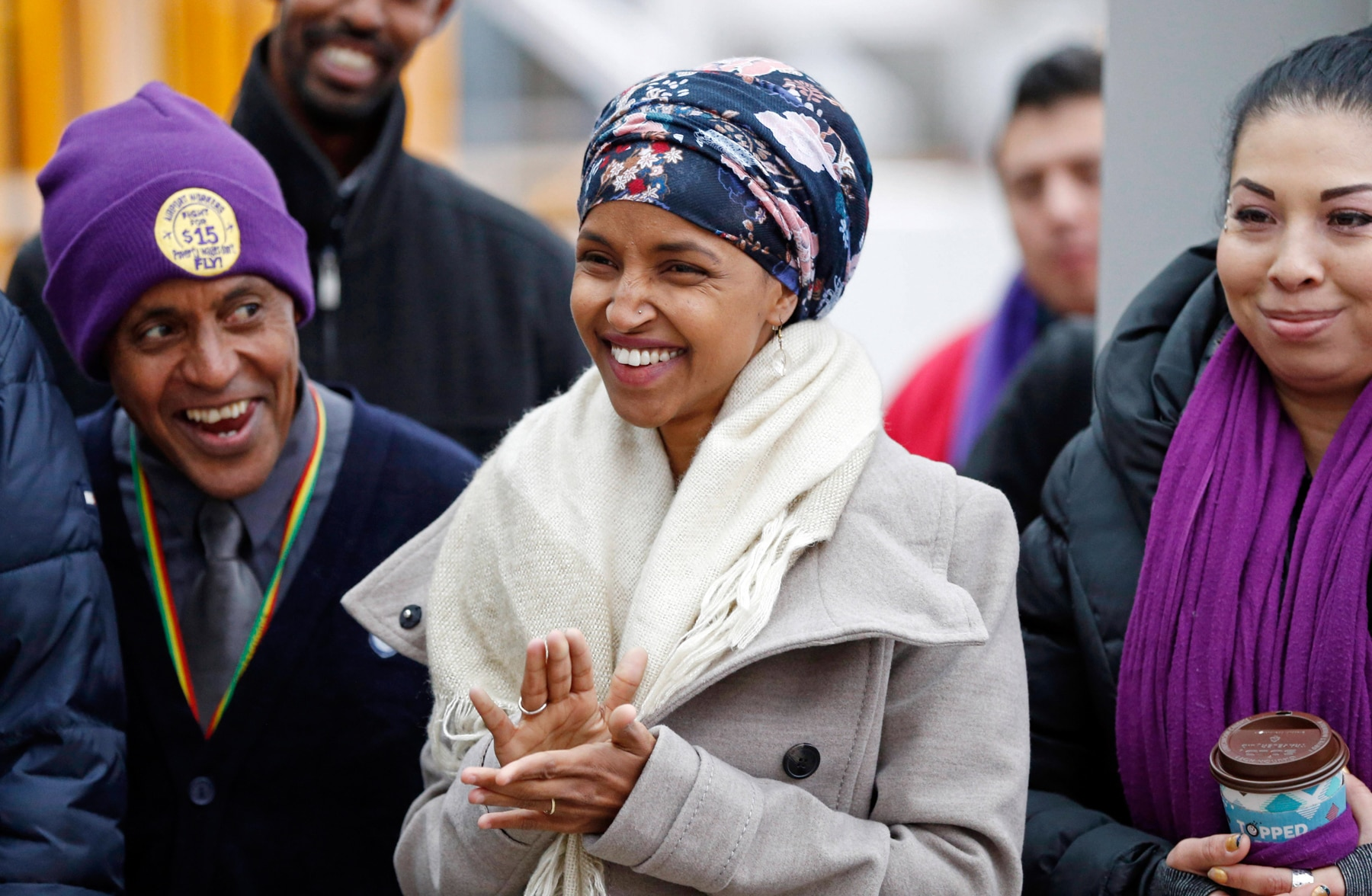 Ilhan Omar in crowd, clapping (© AP Images)