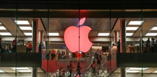 Red apple sign in store window (© AP Images)