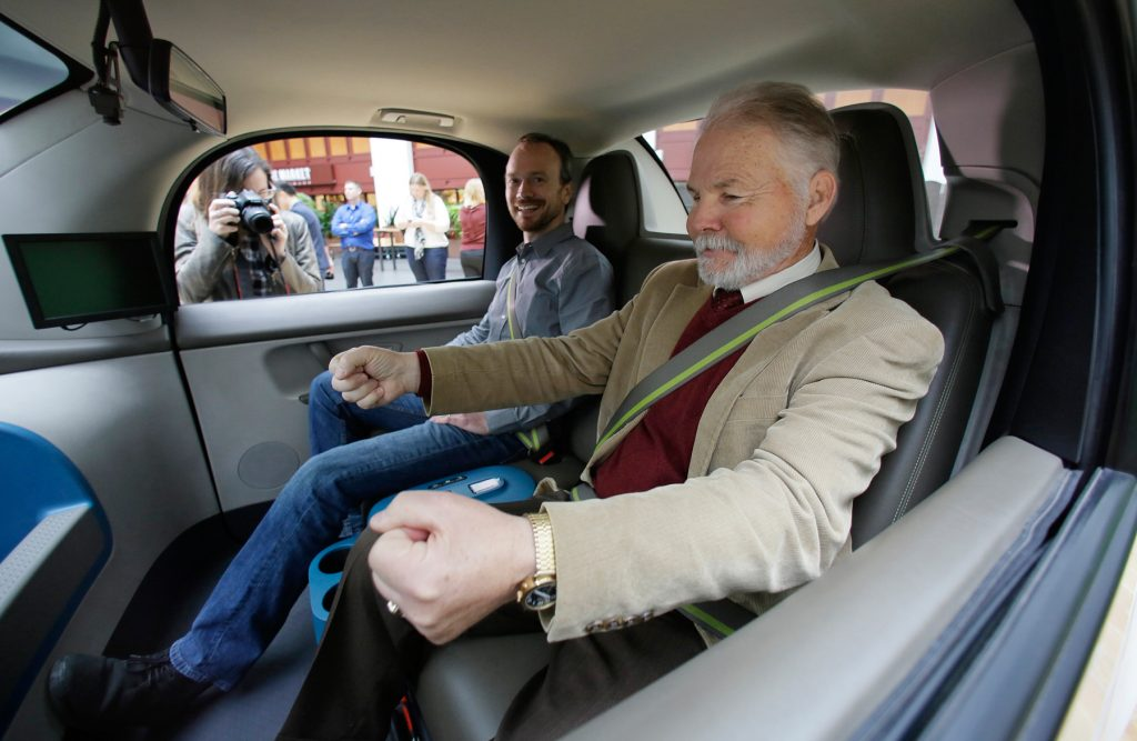 Two men sitting in self-driving car (© AP Images)