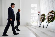 Two men walking toward wreaths of flowers attended by man in uniform (© AP Images)