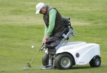 Man without legs braced and positioned by machine for golfing (© AP Images)