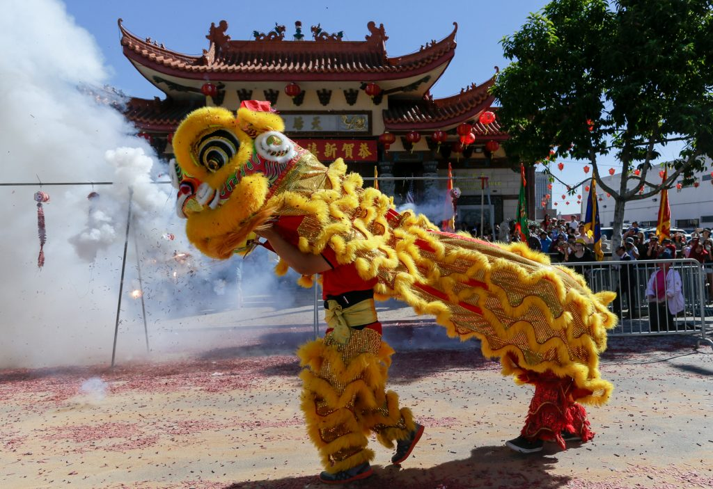 People in Chinese lion costume (© AP Images)