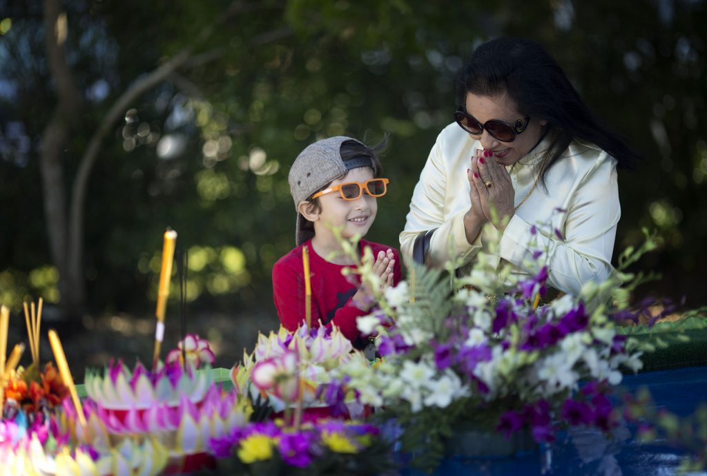 Two people praying near flowers and incense (© AP Images)