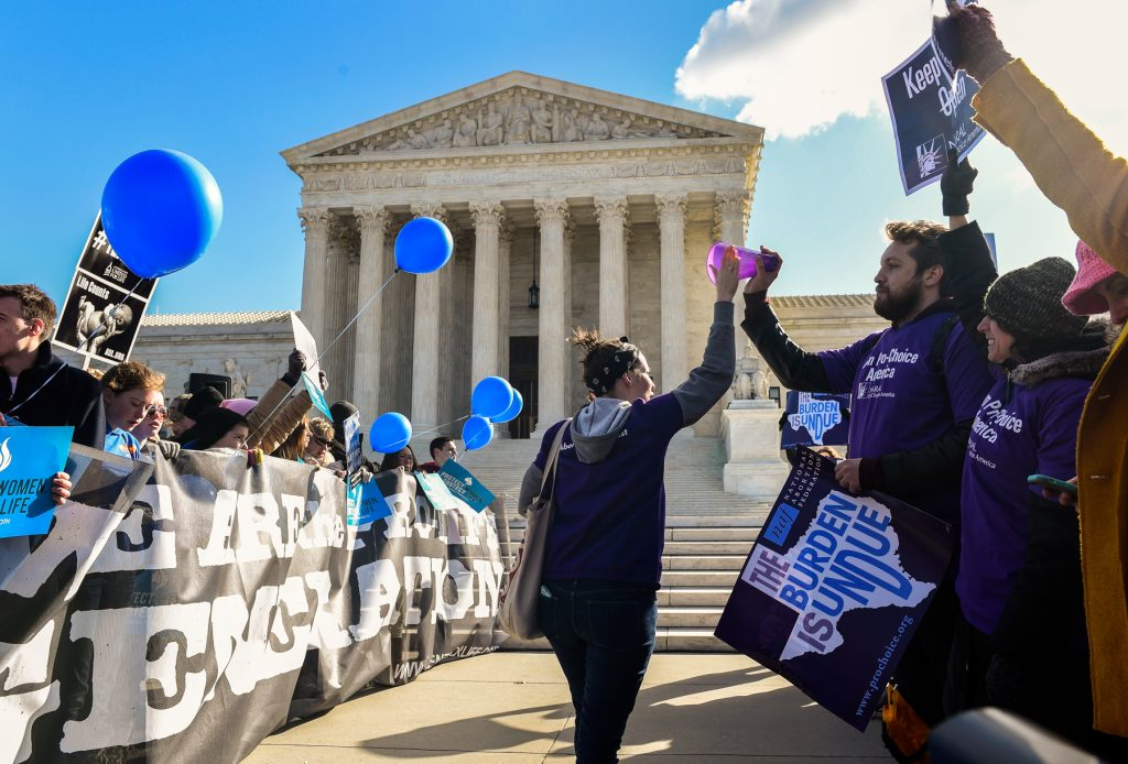 Supreme Court building with groups of people in front of it (© AP Images/Susan Walsh)