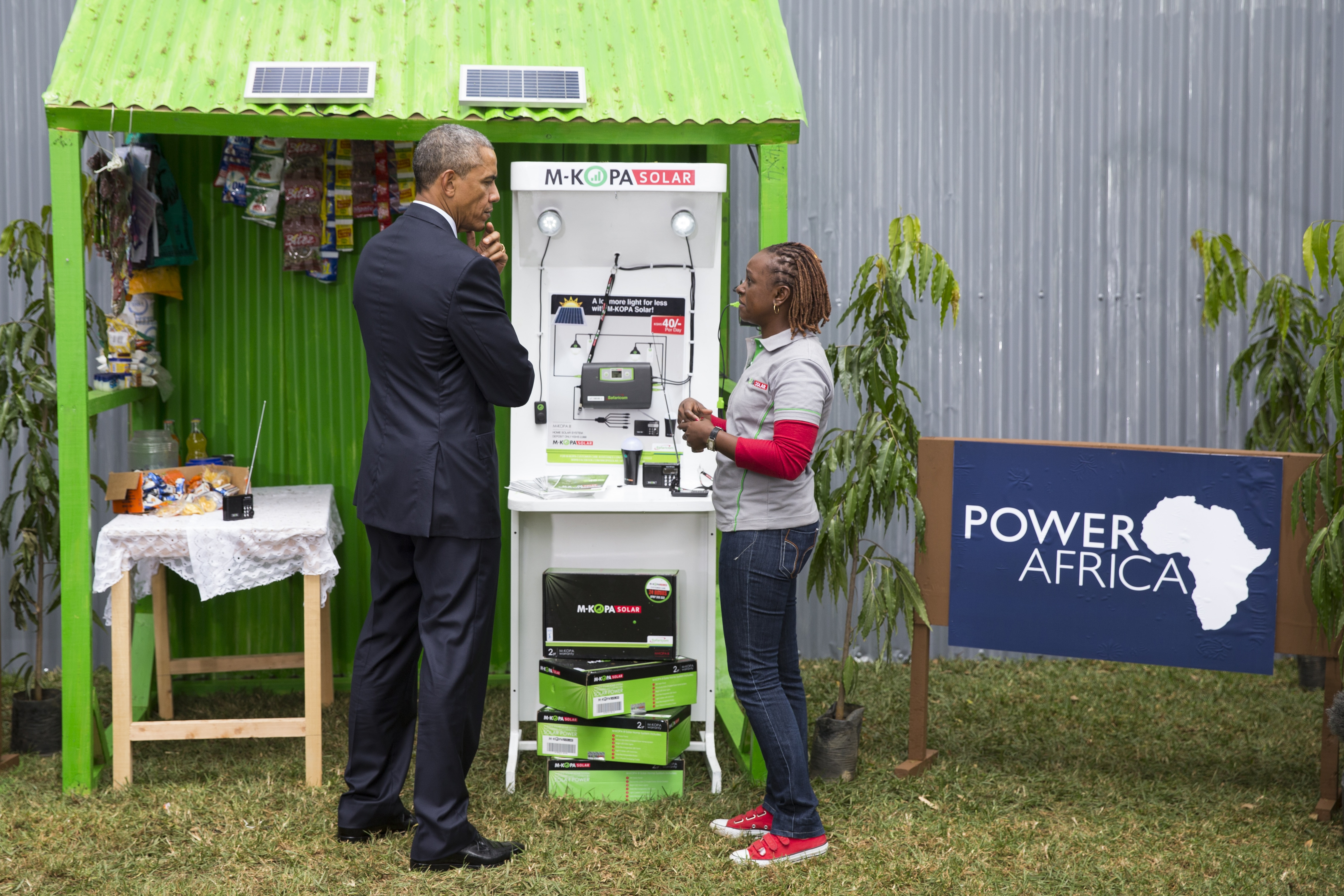 President Obama and a young woman at a solar power exhibit booth (© AP Images)
