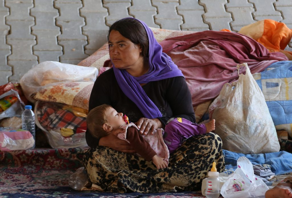 Woman holding child in her lap (© AP Images)
