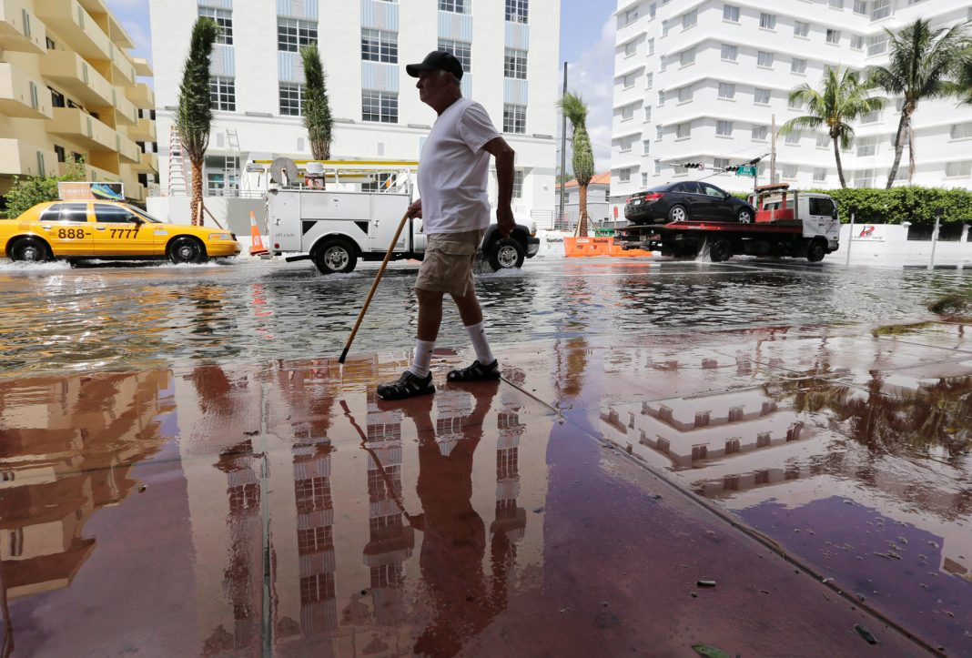 Man walking along flooded street (© AP Images)
