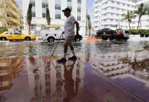 Homem anda por rua inundada (© AP Images)