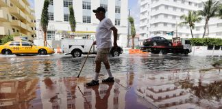 Man walking along flooded street (© AP Images)