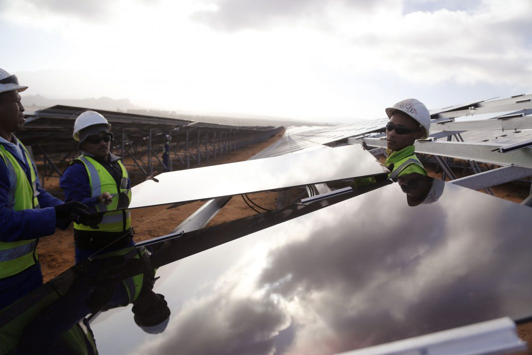 Três homens seguram painel solar (© AP Images)
