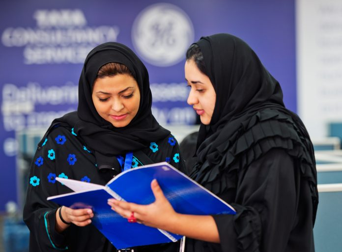Two women looking at booklet (Courtesy TCS/GE)