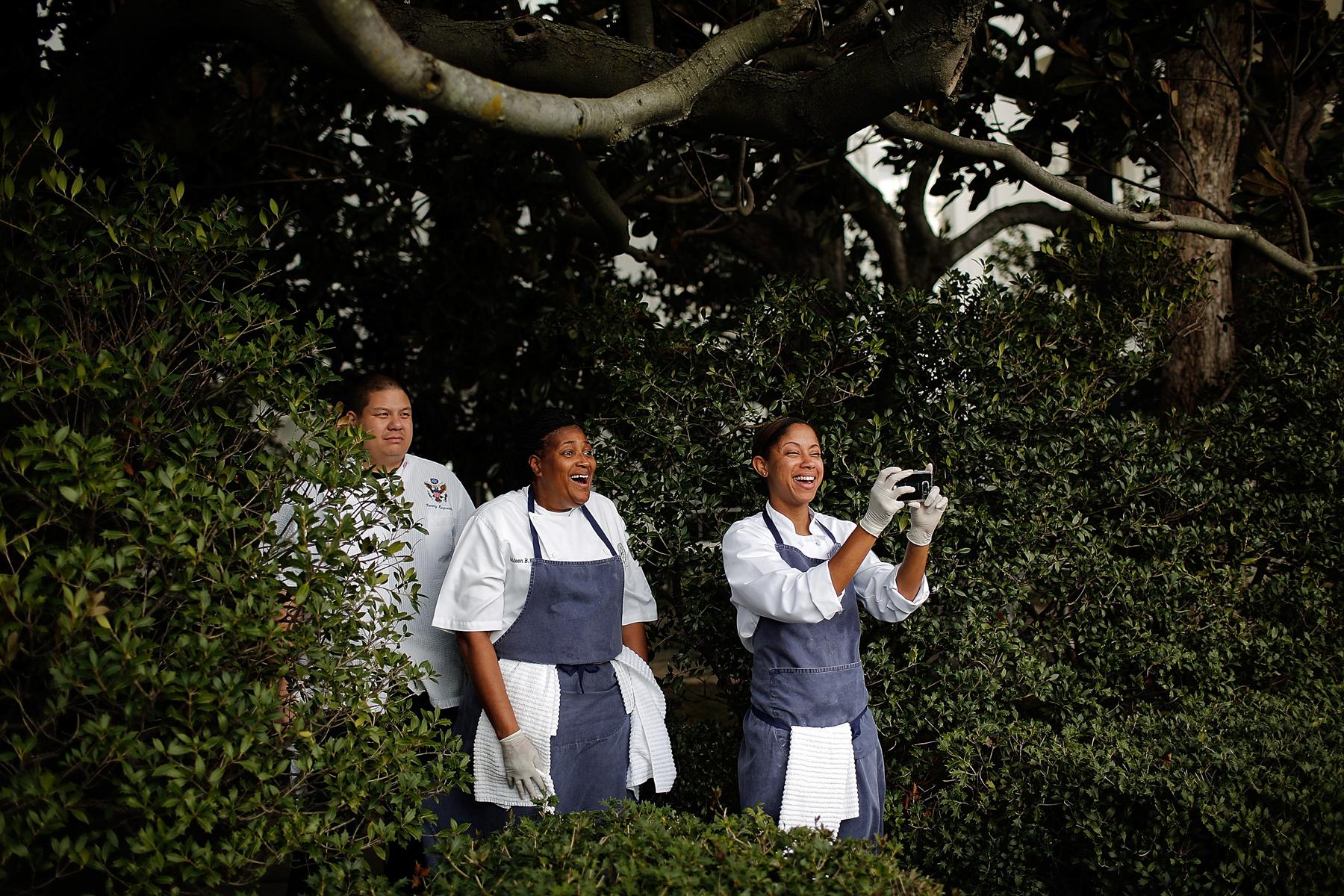 Tres personas junto a unos arbustos, una tomando una foto con una cámara (© Getty Images/Win McNamee)