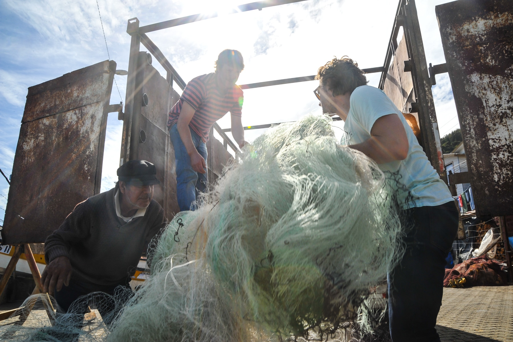 Three people loading fishing net onto truck (© Bureo)
